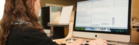 A woman viewing sheet music on a computer screen.