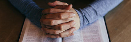 Hands folded in prayer over a bible.