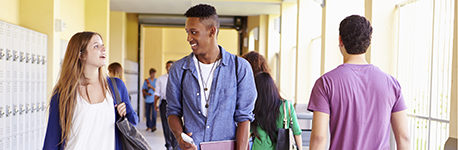 Group of high school students walking along hallway chatting.