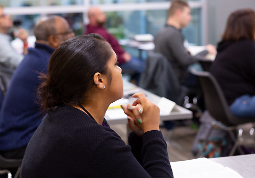 A degree completion student listens in class