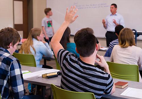 An undergraduate student raises a hand during class