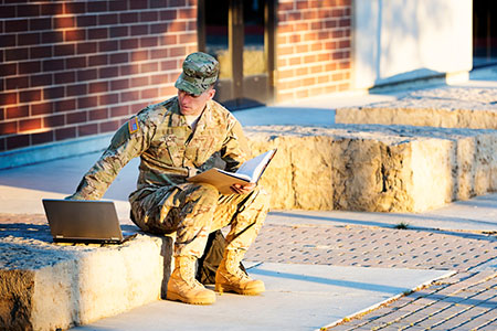 An American soldier studying on a laptop.