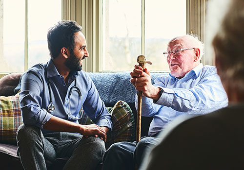 A social worker gives care to an older gentlemen