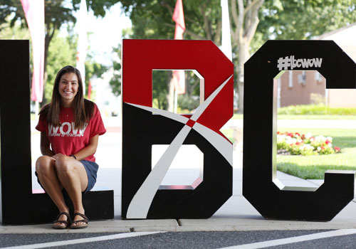 A student sits in large LBC letters
