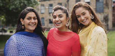 Three woman of various ethnicity's are wearing sari's of different colours are standing laughing.